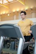 Man using treadmill in gym Stock Photos