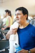 Older man toweling off in gym Stock Photos