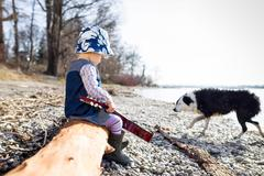 Boy playing with guitar on log Stock Photos