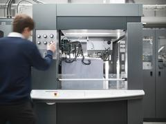 Printer adjusting paper feed on press in printworks Stock Photos