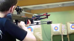 Handsome man with a bow and arrowss shoots with a crossbow in the dash in Stock Footage