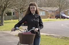 Young attractive parish priest using a bicycle as transport - stock photo