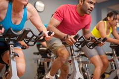 People using spin machines in gym Stock Photos