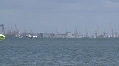 Ferry boat passing in the water with industrial harbor in the background Stock Footage