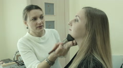 The makeup artist tells as she applying cosmetics Stock Footage