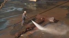 Worker washing ship anchors in dry dock Stock Footage