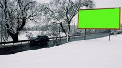 Snowy landscape and billboard at a road where go cars Stock Footage