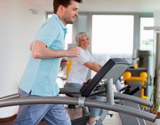 Man using treadmill in gym Stock Photos