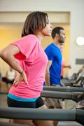 Woman using treadmill in gym Stock Photos