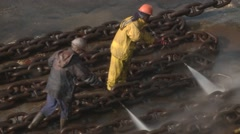 Workers washing ship and anchor chain in dry dock Stock Footage