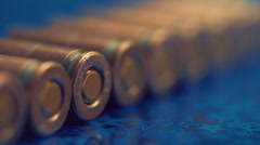 Row of new, not shooting bullet caliber 9mm on reflective surface. Closeup Stock Footage