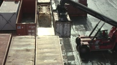 Forklift tractor moving metal shipping containers in harbor Stock Footage