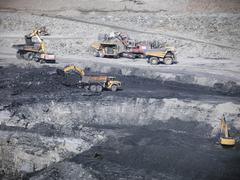 Digger loading coal into dumper truck in opencast coalmine Stock Photos