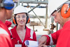 Workers talking at oil refinery Stock Photos