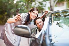 Stock Photo of Woman giving directions to man in car