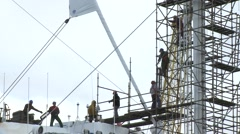 Workers assemble scaffold on a ship mast in a dry dock port Stock Footage