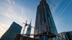 Sunset timelapse of skyscrapper construction works, pan Stock Footage
