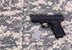 Camouflage battle dress uniform with ID tags and pistol - stock photo