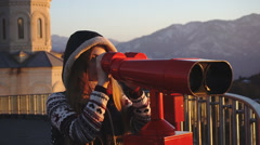 Tourist looking at city through coin-operated binoculars at sunset, medium shot Stock Footage