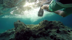 POV below man's waist swimming with flippers over rocks with sea urchins Stock Footage