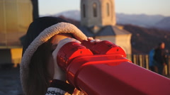 Tourist looking at city through coin-operated binoculars at sunset, tight shot Stock Footage