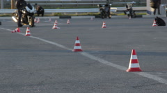 Man puts traffic cones on the motorcycle training ground Stock Footage