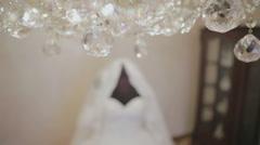 Elegant white wedding dress near the crystal chandelier Stock Footage