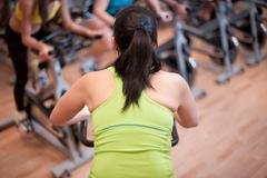 Woman using spin machine in gym Stock Photos