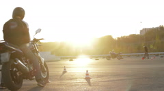 Motorcyclists standing with a motorcycle at sunset Stock Footage