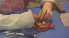 Kid is Fixing a Smile to a Cat Shaped Candy Learning to Make Sweets Excursion Stock Footage