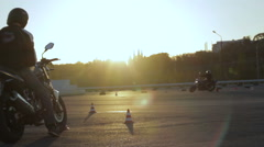 Motorcyclists compete on the track passing speed timing with the timer at sunset Stock Footage