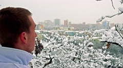 Young man stands and has a nice view on town across snowy trees Stock Footage