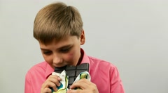 Caucasian Teen SchoolBoy Child eating a chocolate bar Stock Footage