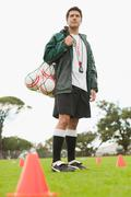 Coach carrying soccer balls on pitch Stock Photos