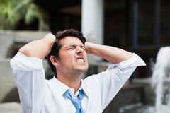 Businessman tearing at his hair - stock photo