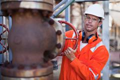 Worker adjusting gauge at oil refinery Stock Photos
