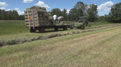 Haying square bales with a tractor and trailer. - stock footage