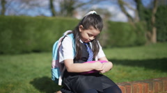 4K Sad little girl alone in schoolyard cheers up when children come to play - stock footage