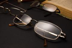 Eyeglasses with magnifying glass on dark surface with books. Stock Photos