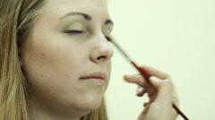 Applying powder using brush on eyelid - stock footage