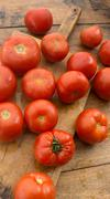 Freshly picked tomatoes, place on wooden chopping board and table. - stock photo