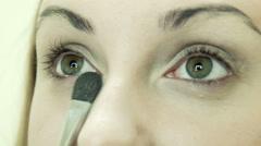 Applying powder using brush on eyelid Stock Footage