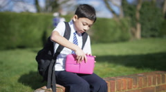4K Sad little boy alone in schoolyard cheers up when children come to play - stock footage