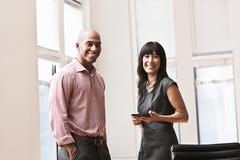 Businessman and businesswoman in office, portrait Stock Photos