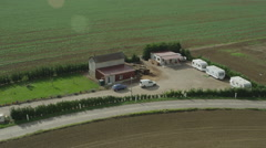 Aerial of vehicles parked in front of farmhouse amidst field the beautiful field Stock Footage