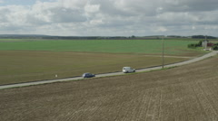 Aerial of vehicles moving on country road amid beautiful fields Stock Footage