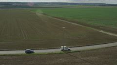 Stock Video Footage of Aerial of vehicles moving on country road amid beautiful fields
