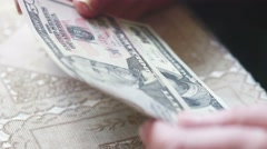 Closeup of senior lady hands with dollar bills, toned color, selective focus - stock footage