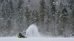 View of a tractor shoveling snow on a field in Hallstatt Stock Footage