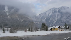 Traun river flowing along houses and mountains on a winter day in Hallstatt Stock Footage